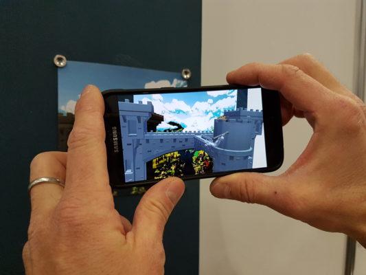 Hände halten ein Smartphone auf dessen Screen AR-Inhalte präsentiert werden